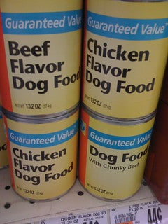 A stack of four cans of dog food on a supermarket shelf